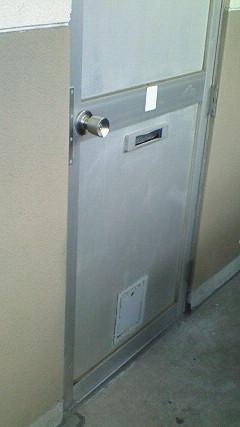 玄関ドアにつくられた牛乳配達の瓶を出し入れする小さな扉